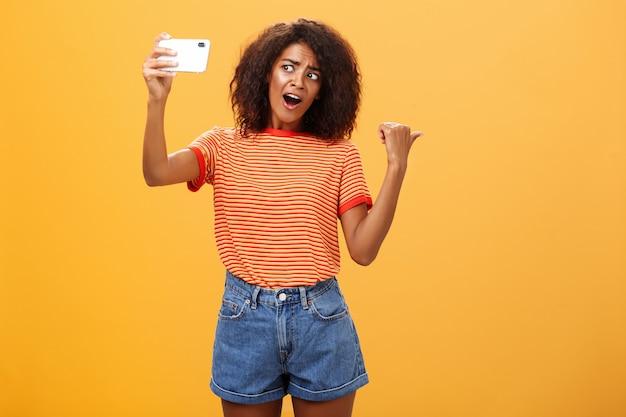 오렌지 벽 위에 다시 가리키는 셀카를 복용 어두운 피부 여자