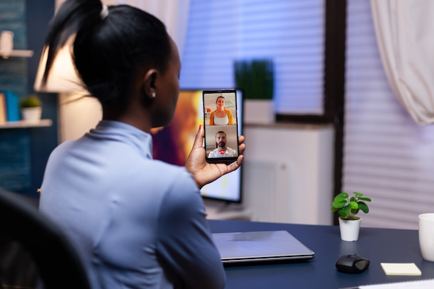 Dark skinned woman talking about project with coworkers late at night in the course of video conference on smartphone. busy employee using modern technology network wireless doing overtime for job.