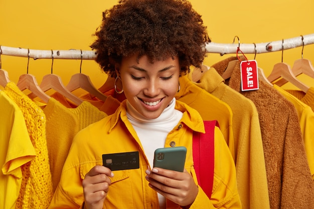 Dark skinned woman uses modern mobile phone and credit card, does online shopping, makes order via internet, inserts bank account information, stands against clothing racks.