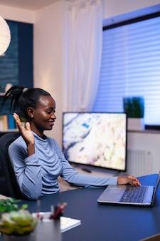 オンライン会議中に机に座っているラップトップのウェブカメラで手を振っている暗い肌の女性。仮想オンライン会議をリモートチームチャットで作業している黒人のフリーランサー。