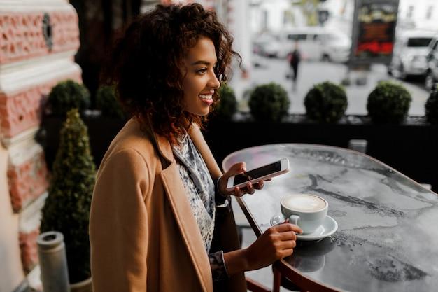 アフロの髪型の浅黒い肌の女性がソーシャルネットワーク経由でニュースフィードやメッセージをチェック