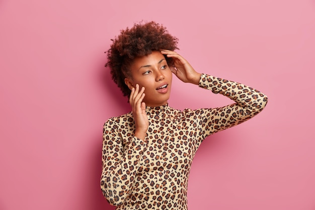 Dark skinned woman with curly hair, looks aside thoughtfully, dressed in stylish leopard outfit