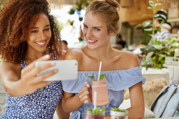 暗い肌の若い女性と友人は前向きな表情を持ち、自撮りをし、スムージーを飲み、カフェテリアでレクリエーションの時間を過ごします。人、レクリエーションの時間とライフスタイルのコンセプト