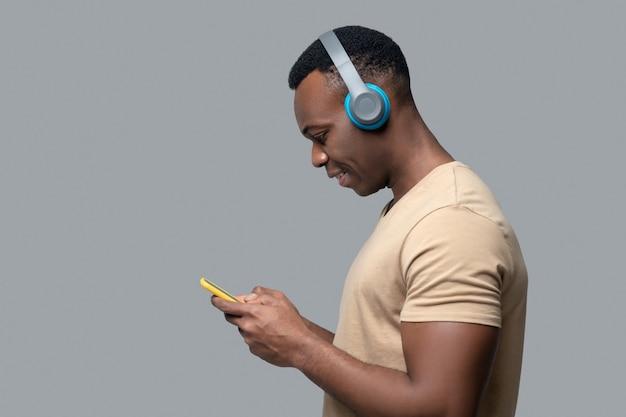 音楽を聴いているヘッドフォンで浅黒い肌の若い男