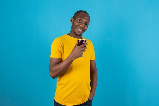 파란색 벽에 와인 한 잔을 들고 노란색 셔츠에 어두운 피부의 젊은 남자