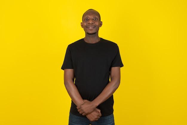 Giovane dalla pelle scura in piedi e in posa sul muro giallo