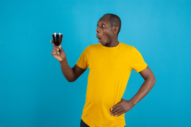 Dark-skinned young man in yellow shirt holding glass of wine on blue wall