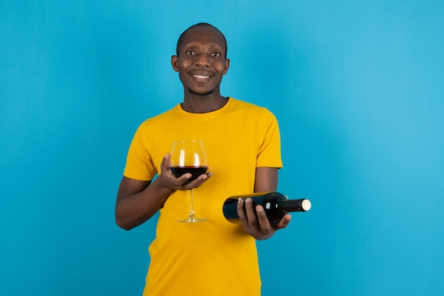 Dark-skinned young man in yellow shirt holding red wine on blue wall