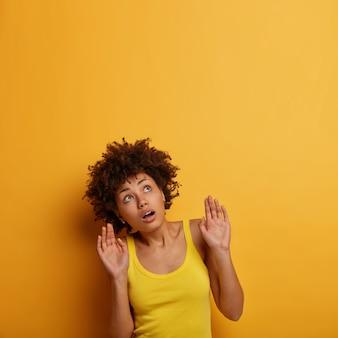 Темнокожая молодая женщина боится чего-то над ней, смотрит вверх с испуганным выражением лица