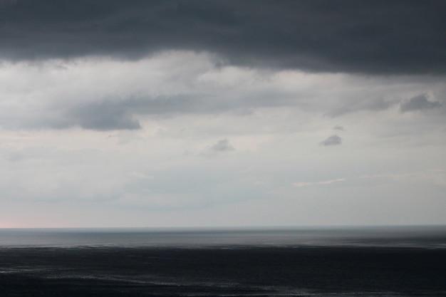 어두운 하늘과 비가 내리기 전에 극적인 검은 구름. 해변에서 오는 비