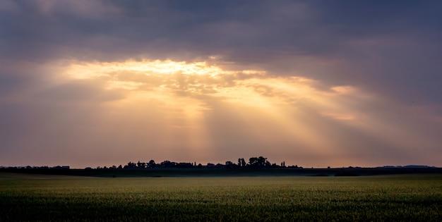 日の出の間に雲と暗い空。太陽の光が暗い雲を突破する_