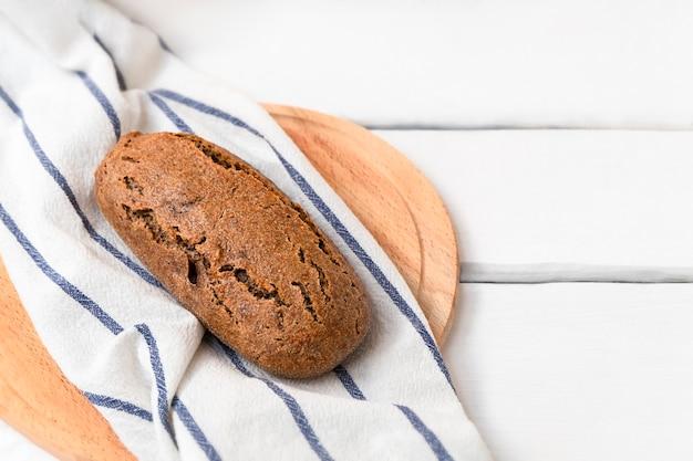 텍스트를 위한 공간이 있는 흰색 나무 테이블에 어두운 사워도우 이콘 빵
