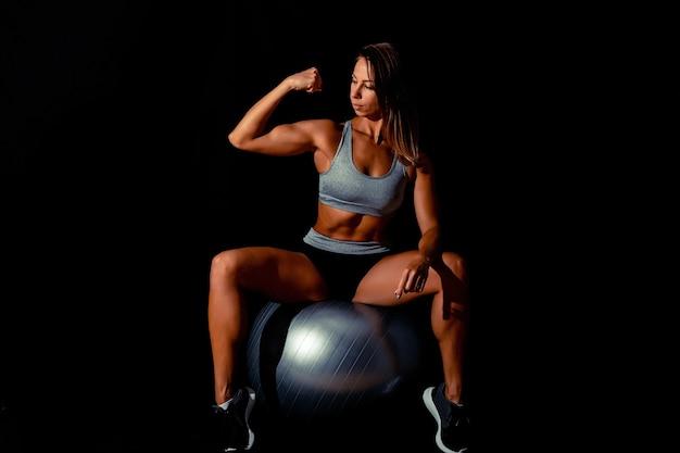 スポーツウェアのダークスポーツセクシーな女の子は、ジムで灰色のフィットボールに腕立て伏せを行います。