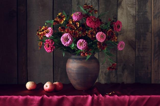 粘土の水差しと果物に花とリンゴの秋の花束と暗い静物
