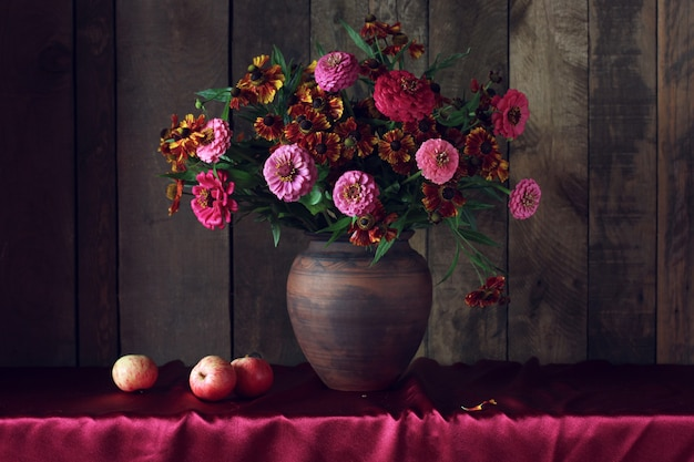 Dark still life with flowers and apples autumn bouquet in a clay jug and fruit