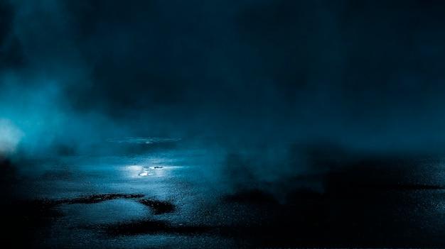 水中の光線の暗い通りの濡れたアスファルト反射抽象的な濃い青の煙のスモッグ空の暗いシーンネオンライトスポットライト