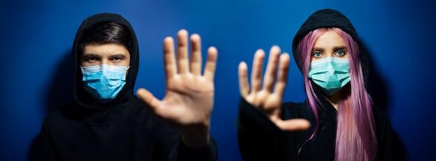 コロナウイルスに対する医療用フェイスマスクを身に着けている若いフード付きのカップル、男と女の暗いスタジオのパノラマの肖像画、幻の青い色の背景にstopジェスチャーを示しています。