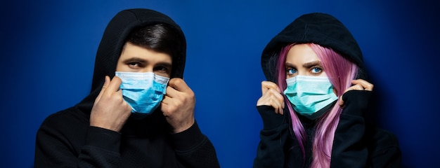 Dark studio panoramic portrait of young hooded couple, guy and girl wearing medical face mask against coronavirus, on background of phantom blue color.