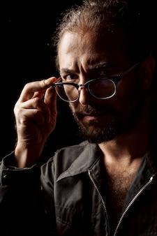 カメラを見ている眼鏡のひげを持つ中年男性の暗いスタジオの肖像画