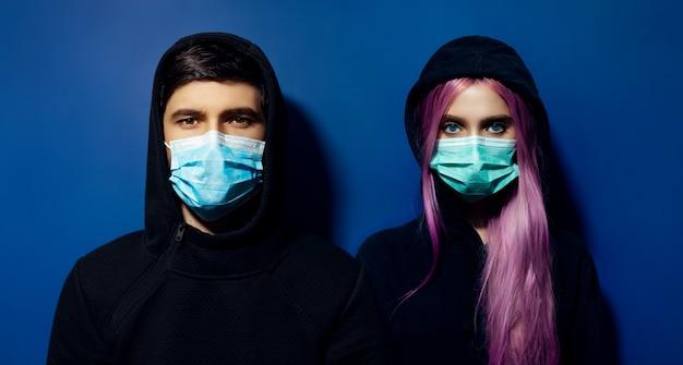 青の背景にコロナウイルスに対して医療インフルエンザマスクを身に着けている若いフード付きのカップル、男と女の暗いスタジオの肖像画。