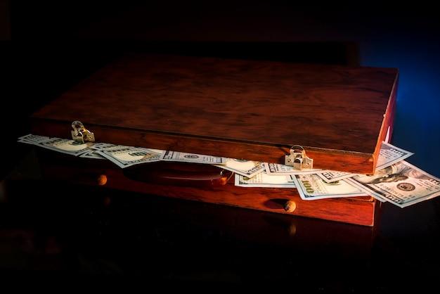 Темный чемодан, полный доллара, изолированных на черном.