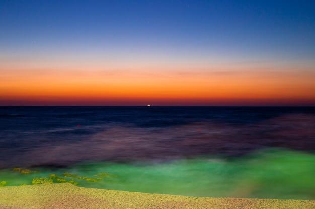 夜遅くに海に沈む夕日