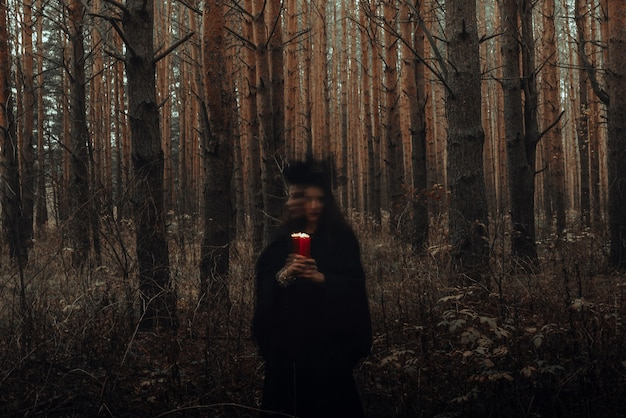 Dark terrible witch with candles in her hands performs an occult mystical ritual in the forest. blurry photo with blurring due to long exposure time