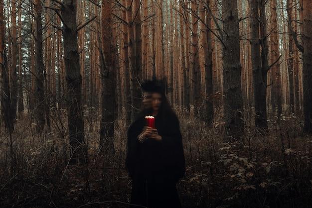 촛불을 손에 들고 어둠의 끔찍한 마녀가 숲에서 신비로운 의식을 수행합니다. 노출 시간이 길어 흐릿한 사진