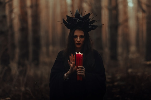 ろうそくを手にした暗黒の恐ろしい魔女が森で神秘的な神秘的な儀式を行う
