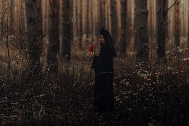그녀의 손에 촛불을 든 어두운 끔찍한 마녀는 숲에서 신비로운 신비로운 의식을 수행합니다.