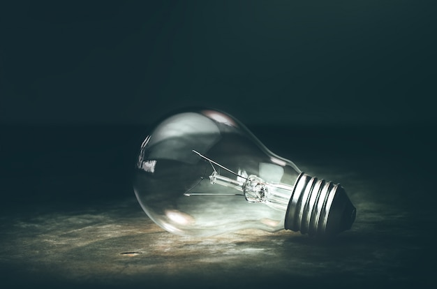 Dark tone lightbulb lamp on the floor dramatic background concept.