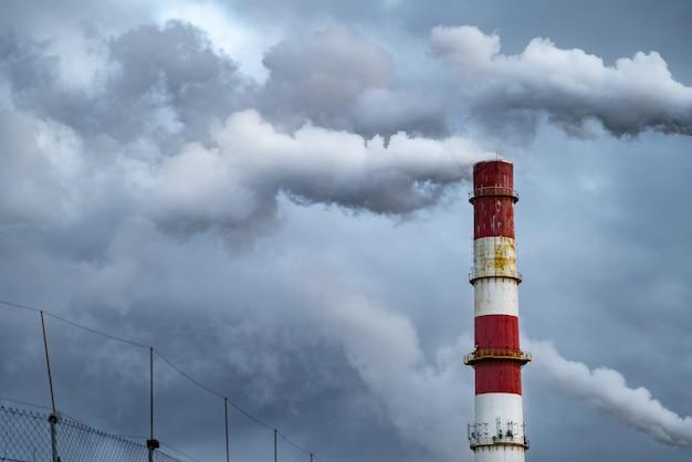 Темные облака токсичного дыма выходят из заводской трубы. Premium Фотографии