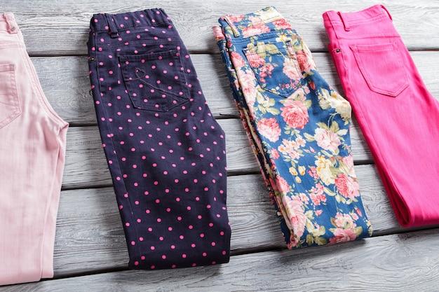 핑크 도트가 있는 다크 팬츠. 플라워 패턴의 폴딩 팬츠. 저렴한 가격의 여아바지. 세련된 디자인의 새로운 의류.