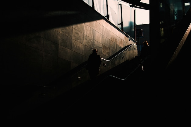 Dark underground area with two people walking down the stairs