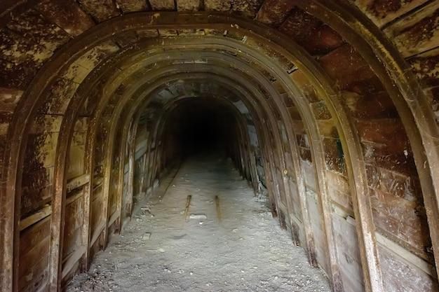Dark underground tunnel with wooden walls in abandoned mine