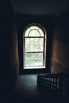 Dark vintage staircase interior in old building, stair with wooden railing, big window with day light