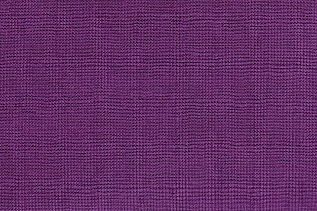 Dark violet background from a textile material with wicker pattern, closeup.