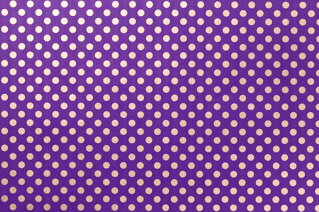Dark violet background from wrapping paper with a pattern of silver polka dot closeup