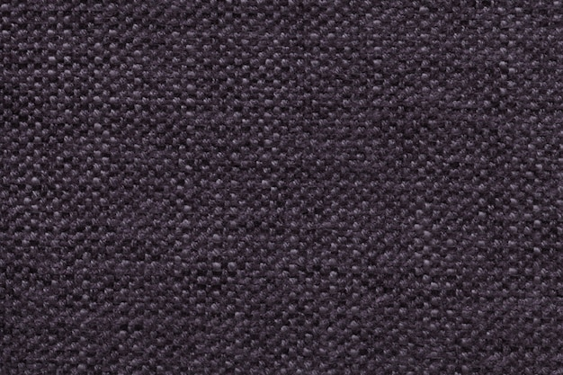 Dark violet knitted woolen background with a pattern of soft, fleecy cloth. texture of textile closeup.