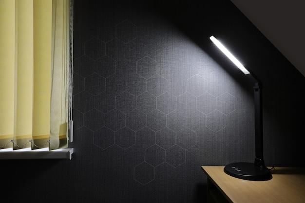現代のledテーブルランプの光で照らされたセルのパターンを持つ暗い壁