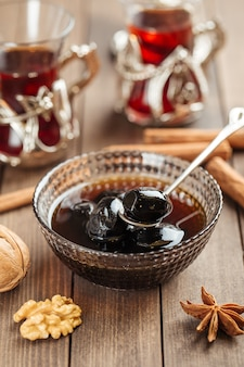 Dark walnut jam in a glass bowl on wooden decorated table