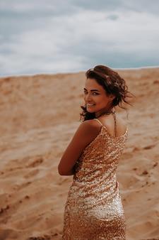 砂丘の砂の間でボリュームのある巻き毛を持つ暗い女性。砂漠の美しい女性