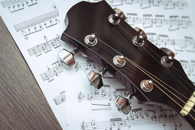 악보에 6개의 현이 있는 어두운 나무 어쿠스틱 기타 목.