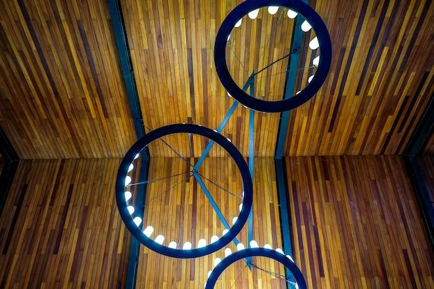 装飾的な丸いシャンデリアの照明設備が付いている暗い木製の天井