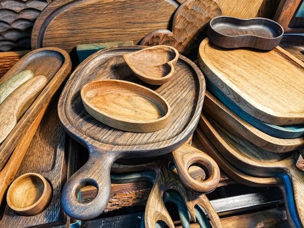 Разделочная доска из темного дерева, посуда и миска в форме сердца.