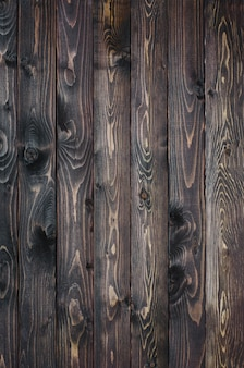 Dark wooden background made of a narrow board, painted in dark brown.