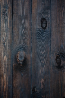 Dark wooden background made of a wide board, painted in dark brown .