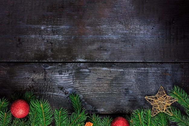 Dark wooden background with fir branches and christmas decorations top view space for text