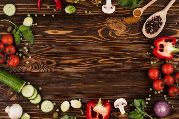 On a dark wooden board are laid out ingredients for an italian dish