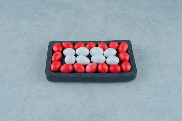 Una tavola di legno scuro piena di caramelle colorate dolci rotonde su superficie bianca